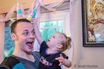 One year old girl trying to get one of her Dad's three unicorn hats at her birthday party.  (MR)