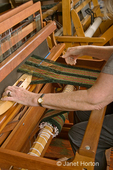 Woman, Marcy, throwing a shuttle of thread to weave a scarf on her loom.