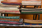 Rack of woven rag rugs ready for sale which Marcy wove on her loom.