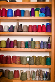 Shelves of thread spools for use in making woven scarves which Marcy weaves on her loom.