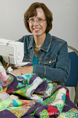 Woman (Mary Beth) piecing a quilt on a sewing machine.  She is a member of St. Joseph Church Quilting Group who donates all of their items to a local charity, Eastside Baby Corner.