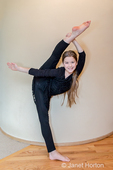 Ten year old dancer girl showing her flexibility by doing a bow and arrow leg hold.