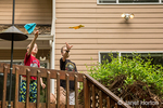 10 and 14 year old boys throwing paper airplanes from a deck.