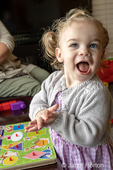 19 month old girl clapping for herself with pride at her ability to put a puzzle together, as her Mom looks on in the background.