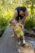 Eatonville, Washington, USA.  Father helping his 18 month old girl wade in the shallow water.
