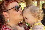 Eatonville, Washington, USA.  Mother kissing her 18 month old daughter on a summer day.