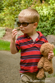Issaquah, Washington, USA.  Two year old boy carrying teddy bear and wearing askew Mom's sunglasses.