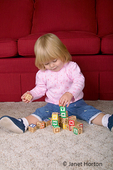 22 month old toddler girl showing pride at being able to build a pile of blocks.