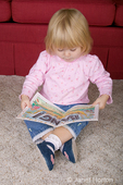 22 month old toddler girl concentrating on reading a book while sitting on the floor.