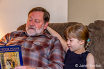 Grandfather reading to his six year old granddaughter