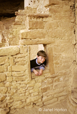 Boy, Mike, peering through window in cliff dwelling in Cliff Palace.