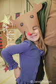 Issaquah, Washington, USA.  Six year old girl showing off her handmade Rudolf hat at a school crafts fair.
