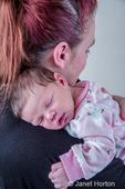 Mother tenderly holding her sleeping twelve day old baby girl.