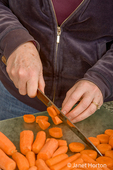Woman chopping carrots with a knife in preparation for blanching and freezing.