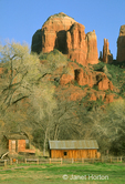 Cathedral Rock spires at sunset with barns, a waterwheel and trees in the foreground