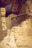 Cliff Palace with poles in wall near ceiling of a room.
