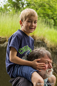 Seattle, Washington, USA.  Seven year old boy getting a piggyback ride from his grandfather. (MR)