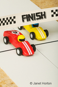 Toy cars racing, with one crossing the finish line