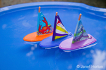 Three toy sailboats sailing in a blue tub of water
