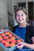 Twelve year old girl holding a pan of 13 bright cupcakes which she just finished decorating.