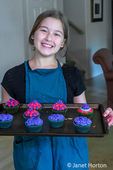 Twelve year old girl holding a pan of 9 bright cupcakes which she just finished decorating.
