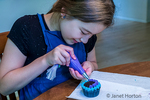 Twelve year old girl decorating a chocolate cupcake using a decorating tube of stiff frosting.