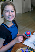 Twelve year old girl showing a chocolate cupcake that she just frosted.