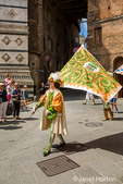 Siena, Italy.   Flag bearer leading a parade to celebrate a child's first Holy Communion.