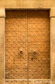 Cortona, Italy.  Decorative wooden door on a stone residence.