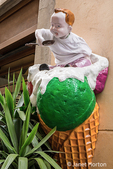 Cortona, Italy.  Humorous ice cream store decoration of a boy sitting on top of a large ice cream cone.  (For editorial use only)