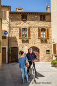 Pienza, Tuscany, Italy.  Local people, one with a bike, stopping to chat near their homes in this UNESCO World heritage site town. (For Editorial Use Only)