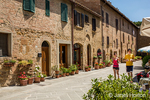 Pienza, Tuscany, Italy.  Tourists with drinks enjoying a walk in this UNESCO World heritage site town.  (For Editorial Use Only)