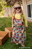 2 Year old girl having fun modeling Grandma's sunglasses and apron outside