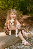 Joanna, a 3.5 year old girl, holding a female Cavalier King Charles Spaniel, Mandy, at 15 weeks old in a wooded setting