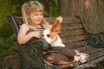 Three year old girl sitting on a wood bench, holding the ear of a fifteen week old Cavalier King Charles Spaniel, Mandy, in a wooded garden setting