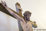 Close-up of top half of a tall statue of Jesus on the Cross (Crucifix) at St. Joseph Catholic Church