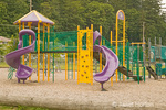 Elementary school-age playground equipment, which is less than 8 feet high and has various climbing equipment and slides