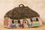 Front of a Tea cozy cottage made of knit and wet-felted sheep's wool with a knitted llama / mohair thatched roof.  Silk ribbon embroidered flowers around about.  Made by Marilyn Romatka.