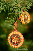 Two Christmas ornament made of corn, seeds and spices glued to a wooden base made by Marilyn Romatka.  These are traditional German Christmas tree decorations.