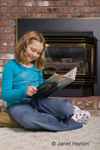 Girl, Lila, reading in front of a gas fireplace in a family room