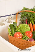 Basket of bulk produce in the sink of a white tiled kitchen
