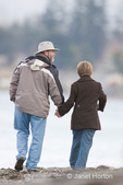 Man and woman holding hands walking on the seashore