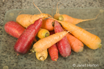 Pile of washed multi-colored carrots on a glass cutting board in the kitchen