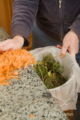 Woman, Kath, pushing carrot peelings into a compost bucket in the kitchen