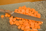 Pile of chopped orange carrots ready for blanching and freezing, with a knife on top in the kitchen