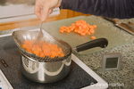 Woman, Kath, pulling expandable strainer out of pot where carrots were being blanched in preparation for blanching in the kitchen