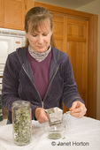 Woman, Kath, grinding home-dried oregano leaves in an herb grinder in the kitchen