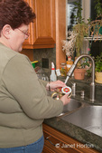 Woman, Phyllis, washing jar rings and lids in preparation for making jam in the kitchen