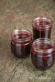 Jars of blackberry jam prior to having household wax poured onto them in the kitchen