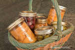 Wicker basket of home canned foods (peaches, olives and cherries) in the kitchen